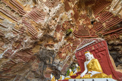 Kaw Goon cave near Hpa-An in Myanmar. Old temple with Buddhas statues and religious carving on limestone rock in sacred Kaw Goon cave near Hpa-An in Myanmar Stock Image