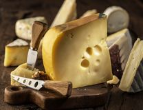 Kawałek krowy mleka Maasdam ser na drewnianej desce Pasmo sery przy tłem zdjęcia stock