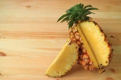 Kawałek świeży dojrzały ananasa cięcie od całej owoc na drewnianym stole Obrazy Royalty Free