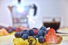Kawałek crostata z jagodami i owoc, za coffe producentem i filiżanką kawa espresso obrazy royalty free