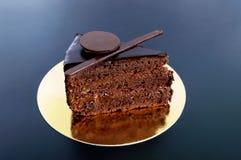 Kawałek czekoladowy tort z czekoladową śmietanką na złotej pielusze Obraz Royalty Free