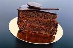Kawałek czekoladowy tort z czekoladową śmietanką na złotej pielusze Obraz Stock