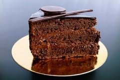 Kawałek czekoladowy tort z czekoladową śmietanką na złotej pielusze Fotografia Royalty Free