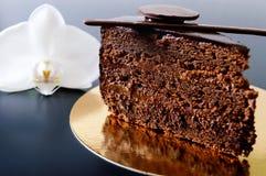 Kawałek czekoladowy tort z czekoladową śmietanką na złotej pielusze z białym storczykowym kwiatem Zdjęcia Stock