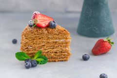 Kawałek domowej roboty miodowy tort z truskawkami, czarnymi jagodami i malinkami na lekkim tle, zdjęcia royalty free