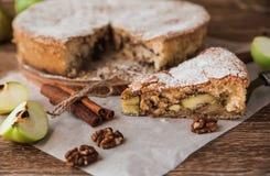 Kawałek jabłczany kulebiak z cynamonem i orzechami włoskimi na drewnianym stole Zdjęcia Royalty Free