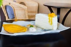 Kawałek mangowy cheesecake na stołowy drewnianym Obraz Stock