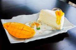 Kawałek mangowy cheesecake na stołowy drewnianym Zdjęcie Royalty Free