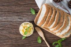 Kawałek masło z sezamowym chlebem na drewnianym tle Zdjęcie Royalty Free
