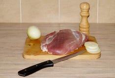 Kawałek mięso z nożem, cebulami i pieprzowym potrząsaczem na tnącej desce, Obrazy Royalty Free