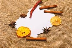 Kawałek papieru na parcianym tle Cynamon, wysuszona pomarańcze i pieprz, gwiazdowy anyż wokoło pustego papieru dla przepisu zdjęcie stock