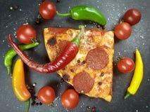 Kawałek pepperoni pizza, czereśniowy pomidor i gorący pieprze, zdjęcie stock