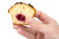 Kawałek słodka bułeczka z faszerujący w męskiej ręce na bielu Fotografia Royalty Free