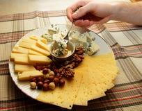 Kawałek ser na rozwidleniu w mężczyzna ręce i biegał puszek z jego miodem Fotografia Royalty Free