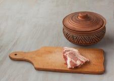 Kawałek surowa wieprzowina na tnącej desce rocznika glinianym garnku i Obrazy Royalty Free