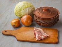 Kawałek surowa wieprzowina na tnącej desce rocznika glinianym garnku i i Zdjęcia Stock