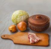 Kawałek surowa wieprzowina na tnącej desce rocznika glinianym garnku i i Obraz Stock