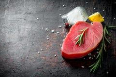 Kawałek uncooked tuńczyka stek z pikantność, rozmarynami i cytryną, obrazy royalty free