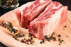 Kawałek wieprzowina na tnącej desce ciemny tło z peppercorn Fotografia Stock