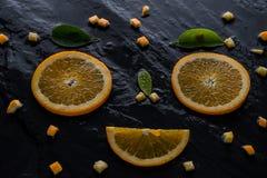 Kawałka nóż na łupku kamieniu i pomarańcze Zdjęcia Royalty Free