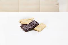 Kawałki biel i dojna czekolada na białym stole Obraz Stock