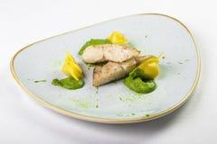 Kawałki bielu i koloru żółtego rybi pierożek w zielonym kumberlandzie na talerzu Obrazy Royalty Free