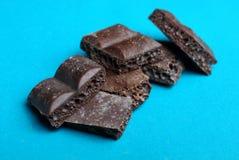 Kawałki brown porowata czekolada na błękitnym tle obraz stock