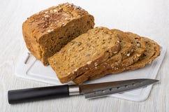 Kawałki chleb z różnymi ziarnami, candied owoc, żyto otręby, nóż na tnącej desce na stole fotografia stock