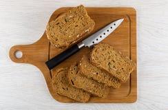 Kawałki chleb z różnymi ziarnami, candied owoc, żyto otręby, nóż na tnącej desce na stole Odgórny widok obraz stock