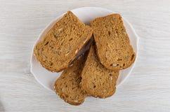 Kawałki chleb z różnymi ziarnami, candied owoc, żyto otręby w talerzu na stole Odgórny widok obrazy stock