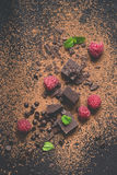 Kawałki ciemna czekolada, proszek, krople i malinki, Karmowy deserowy tło zdjęcie stock