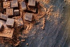 Kawałki ciemna gorzka czekolada z kakaowym proszkiem na drewnianym tle Karta z przestrzenią dla teksta fotografia royalty free