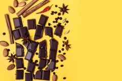 Kawałki czekolada, cynamon, pikantność i migdały na żółtym tle, obraz stock