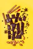Kawałki czekolada, cynamon, pikantność i migdały na żółtym tle, zdjęcia stock
