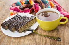 Kawałki czekoladowy gofr zasychają w talerzu, filiżanka herbata obraz stock