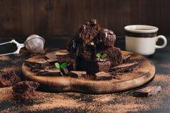 Kawałki czekoladowy tort nalewają ciekłą czekoladę, nowi liście, kawa Selekcyjna ostrość obrazy stock