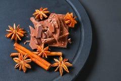 Kawałki czekolady, cynamonowego i gwiazdowego anyż na zmroku popielatym stole, obrazy stock