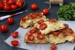Kawałki focaccia z czereśniowymi pomidorami lokalizują na pergaminie na ciemnym tle obrazy stock