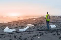 Kawałki lód na czarnym piasku, naturalny szczegół, Iceland Mężczyzna pozycja na czarnej plaży Obrazy Stock