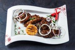 Kawałki piec na grillu baranów barany segregujący na białym talerzu Z cebulami, chili czosnkiem, pieprzami, i zdjęcia stock