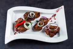 Kawałki piec na grillu baranów barany segregujący na białym talerzu Z cebulami, chili czosnkiem, pieprzami, i obraz stock