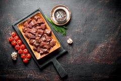 Kawałki surowa wątróbka na tnącej desce z pomidorami i pikantność zdjęcie stock
