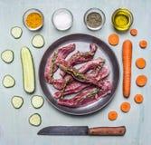 Kawałki surowy baranek z ziele w niecce z pokrojonym ogórkiem i marchewką z nożem oliwią różnorodność seasonings na drewnianym ni fotografia stock