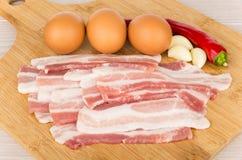 Kawałki surowy bekon, jajka i chili pieprze na pokładzie, Obraz Royalty Free