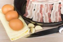 Kawałki surowy bekon w obsady żelaznej smaży niecce, jajka Obraz Stock