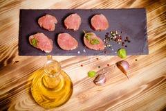 Kawałki surowy mięso na talerzu łupkowe ziele pikantność i oliwny oi Zdjęcie Stock