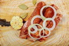 Kawałki surowy wieprzowina stek z pikantność i ziele z czosnkiem, cebule, sól i pieprz na jaskrawym białym drewnianym tle w wierz zdjęcia royalty free