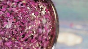 Kawałki wysuszeni purpura kwiatu płatki mieszają łyżką w szklanym pucharze zbiory wideo