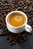 Kawa espresso na kawowych fasoli tle, odgórny widok, pionowo Fotografia Stock