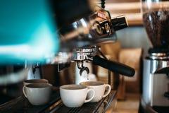 Kawa espresso przepływy zestrzelają od kawowej maszyny wewnątrz dwa filiżanka kawy obrazy royalty free